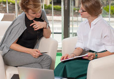 Team work process. Two women with laptop in office. Business women having meeting around table in office Stock Image