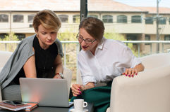 Team work process. Two women with laptop in office. Business women  having meeting around table in office.  Business concept Royalty Free Stock Image