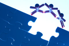Team work on solving puzzle problem Stock Image
