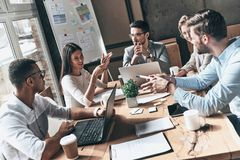 Team at work. Top view of young modern people in smart casual we. Ar discussing business while working in the creative office stock photo