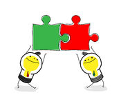 Team work. Two business bulb-man hold puzzlea and work together Stock Images