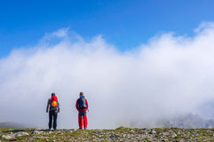 Team work. Team of two young backpackers on top of a mountain Stock Image