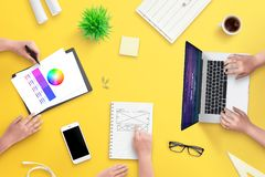 Team work on web design project. Top view, flat lay scene with laptop royalty free stock photos