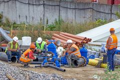 Workers at break and collect pipeline. A team of workers at the construction site collects elements of the pipeline royalty free stock images