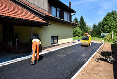 Team of Workers making and constructing asphalt road constructio. N with steamroller. The top layer of asphalt road on a private residence house driveway Stock Photo
