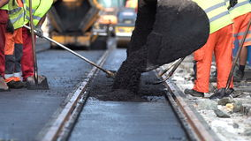 Steamroller workers construct asphalt road and railroad lines. Team of workers put the hot asphalt on a street along tram car`s railroad lines. Small steamroller stock video