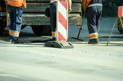 Team of workers put the hot asphalt to pavement street selective focus. Royalty Free Stock Images