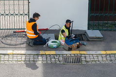 Team of workers working on implementation of fiber optic cables. PARIS, FRANCE - MAR 24, 2017: Team of workers from telecomunication internet provider company Royalty Free Stock Photography
