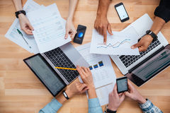 Team working for financial report using laptops and smartphones. Team of colleagues working for financial report using laptops and smartphones Stock Photo