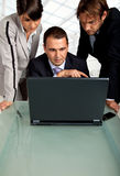 Team working together. Team of three business people , looking at the monitor of a laptop Royalty Free Stock Images
