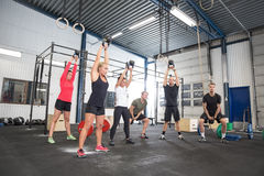 Team workout with kettlebells at fitness gym. Group training with personal trainer and instructor at a fitness center. Kettlebell weight workout at the gym Royalty Free Stock Image