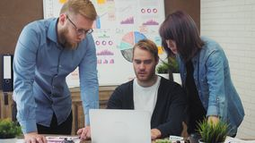 Team of young business managers analyzing data using computer in the office stock footage