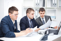 Team of young business men doing some paperwork Royalty Free Stock Image