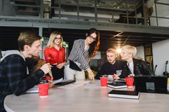 Team of young business professionals using technology in an informal meeting engaged on architect design. International royalty free stock image