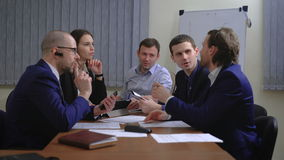The team of young businesspeople. They work together with the documents and figures. In the office. stock video footage