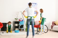 Team of young cleaning service professionals at work. Indoors stock photo