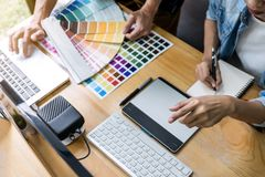 Team of young colleagues creative graphic designer working on color selection and drawing on graphics tablet at workplace, Color. Swatch samples chart for royalty free stock photo