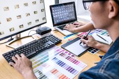 Team of young colleagues creative graphic designer working on color selection and drawing on graphics tablet at workplace, Color. Swatch samples chart for stock photos