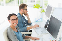 Team of young designers working at desk with woman smiling at camera Royalty Free Stock Photography
