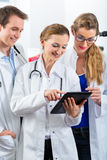 Team of young doctors in clinic with tablet computer Royalty Free Stock Images