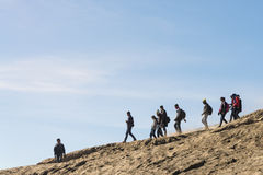 Team of young hikers going down the mountain slope in orderly fashion Royalty Free Stock Photo