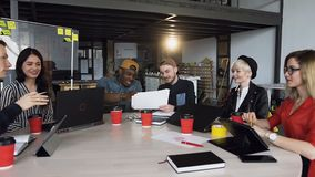 Team of young hipster working together on the new business plan. Team of young hipster people in stylish casual clothes working together on the new business stock video