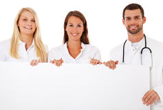 Team of young medical professionals. Behind white placeholder. All on white background stock photos