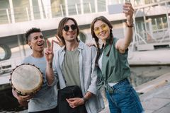 Team of young musicians with instruments taking selfie stock photo