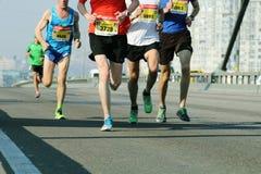 Teamagenten in spoor Marathon lopend ras, mensenvoeten op stadsweg Marathon door de wegen van de stad stock foto