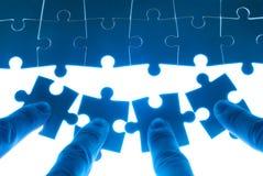 Teamarbeit über das Lösen des Puzzlespielproblems Lizenzfreies Stockbild