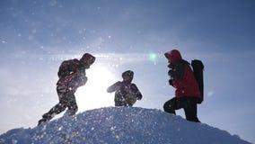 Teamarbeit und -sieg Touristen kommen, vom schneebedeckten H?gel zu ?bersteigen und freuen sich am Sieg gegen Hintergrund eines g stock footage