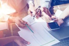 Teambrainstorming Vermarktungsplanuntersuchung Schreibarbeit und Handy stockfoto