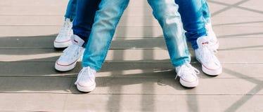 Teambuilding, τρία ζευγάρια των ποδιών στα ίδια παπούτσια και τζιν επάνω Στοκ φωτογραφία με δικαίωμα ελεύθερης χρήσης