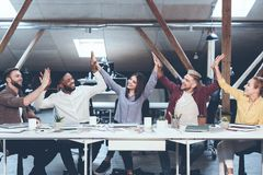 Teambuilding concept. Colleagues joining hands together, sitting in line royalty free stock photography