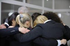 Teamgebäudeereignis: Gruppenumarmung im Büro Lizenzfreie Stockfotografie