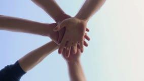 Teamhanden op elkaar Vele handen die op hemelachtergrond samenhouden 6 mensen