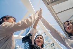 Teaming de mulheres do negócio acima e ter altamente cinco ao elogio acima do espírito de equipe fotos de stock royalty free