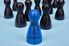 Teamleader mit seinem Team Symbol für Führung mit Spielzahlen in den blauen und schwarzen und gezogenen Anzugselementen Lizenzfreies Stockbild
