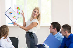 Teamleden die aandachtig aan een bedrijfsvrouw luisteren die a houden Stock Afbeeldingen