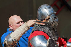 Teammate helping to put on the knight the armors before battle Royalty Free Stock Photo