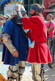 Teammate helping to put on the knight the armors before battle Royalty Free Stock Photography