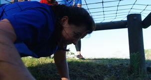 Teammates applauding woman while crawling under net stock video