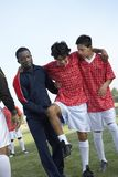 Teammates Carrying Injured Soccer Player Stock Photo