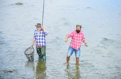 Teammates. male friendship. family bonding. father and son fishing. summer weekend. mature men fisher. two happy