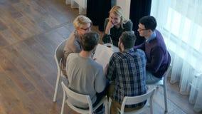 Teammededeling, groep van vijf mensen die iets bespreken met glimlach terwijl het zitten bij de bureaulijst stock videobeelden