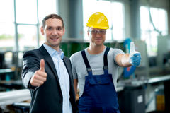 Teamplayer in factory with thumbs up Royalty Free Stock Image