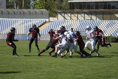 Teams for American football against the backdrop of a green field. Playing American football at the stadium. Match on American football. Men play the ball in a Royalty Free Stock Photo