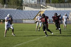 Teams for American football against the backdrop of a green field. Playing American football at the stadium. Match on American football. Men play the ball in a Stock Images