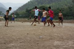 Teams of teenage and young boys playing soccer. Football on a dusty dirt field, evening time in Northern Thailand, Southeast Asia royalty free stock images