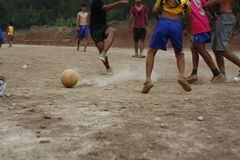 Teams of teenage and young boys playing soccer. Football on a dusty dirt field, evening time in Northern Thailand, Southeast Asia royalty free stock image